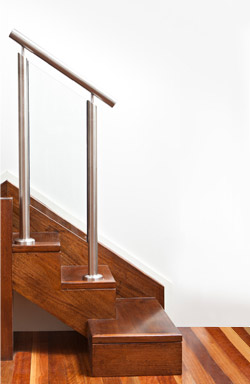 Stained hardwood, flush finished with 50mm round stainless steel handrail, recessed posts and 10mm clear glass balustrade
